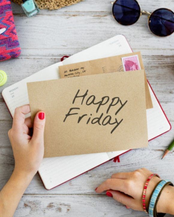 A hand holding a piece of paper with the words &#34Happy Friday&#34 on it over a notepad and various