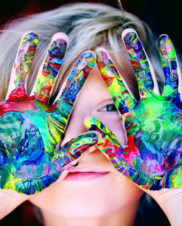 Child holding Multicolored Hands covered in paint over his face