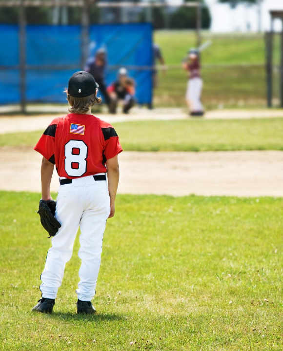 right fielder looking into the infield at a little league baseball game