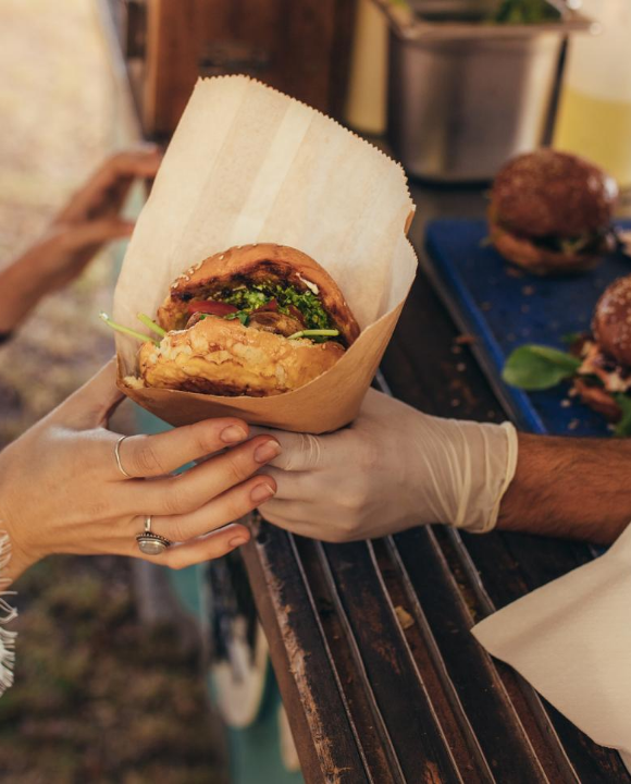 Closeup of Women's hand reaching for a burger at food truck