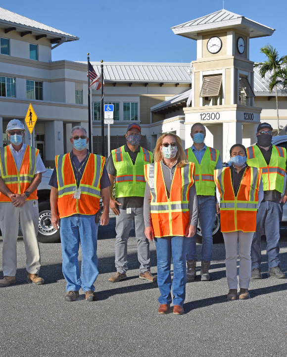 Wellington employees wearing safety vests posing in front of cars at village hall