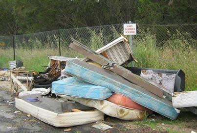 Illegal dumping of mattresses and debris on side of the road